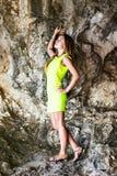 站立在黑暗的洞的石头的美丽的妇女 图库摄影