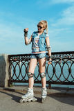 站立在晴朗的明亮的光的直排轮式溜冰鞋的女孩 体育生活方式 库存图片