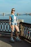 站立在晴朗的明亮的光的直排轮式溜冰鞋的女孩 体育生活方式 免版税图库摄影