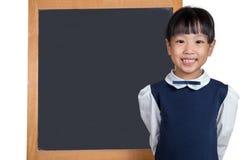站立在黑板前面的亚裔中国小女孩 免版税库存图片