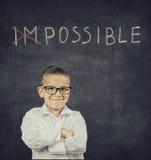 站立在黑板前面的聪明的微笑的男孩 免版税图库摄影