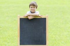 站立在黑板的愉快的小男孩 复制文本的空间 库存照片