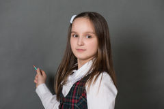 站立在黑板的校服的女孩 库存照片