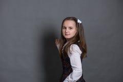 站立在黑板的校服的女孩 图库摄影