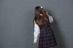 站立在黑板的校服的女孩 免版税库存图片