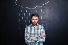 站立在黑板背景的拉长的雨下的严肃的人 免版税库存照片