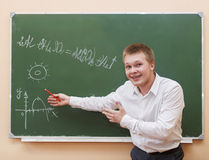 站立在黑板附近的学生男孩 库存图片