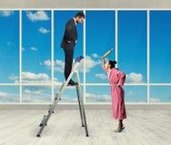 站立在活梯的不满意的人 免版税库存图片