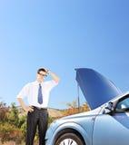 站立在他残破的汽车附近和认为怎样的商人做 免版税库存照片