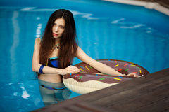 站立在水池的蓝色游泳衣的皮包骨头的女孩 免版税库存照片