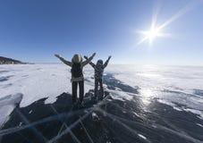 站立在冻湖冰的两个女孩用他的手 贝加尔湖西伯利亚俄罗斯 接受自然以开放的人们 免版税库存图片