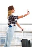 站立在玻璃墙背景的帽子和手提箱的妇女和做selfie 装在口袋里一本护照和一张票 图库摄影