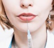站立在他的一件白色长袍的办公室和拿着在注射器的美丽的年轻美容师一根针在嘴唇附近 背景医生查出的白人妇女 库存图片
