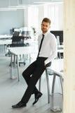 站立在他的办公室的年轻商人画象 免版税库存图片