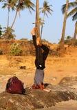 站立在他的在海滩的头的印地安人果阿 Sirsasana姿势是瑜伽asanas `国王`  库存照片