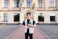 站立在他的大学前面的背景和拿着学生笔记本的男孩 免版税库存照片