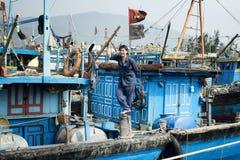 站立在他的小船的微笑的渔夫 库存照片