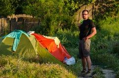 站立在他的帐篷旁边的旅客 免版税库存照片