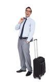 站立在他的手提箱旁边的笑的商人 免版税库存照片