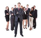 站立在他的队前面的资深业务经理 免版税库存图片