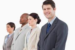 站立在他的队旁边的微笑的商人 库存图片