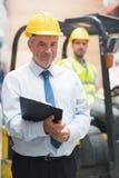 站立在他的雇员前面的经理 免版税库存照片