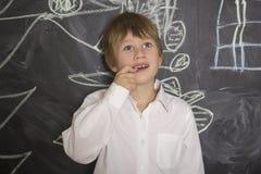 站立在画的黑板附近的小男孩 举行在嘴的手指 免版税库存照片
