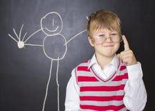 站立在画的黑板附近的小男孩 免版税图库摄影