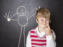 站立在画的黑板附近的小男孩 库存图片