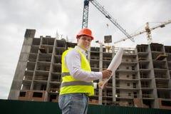 站立在建筑工地和检查bluep的安全帽的工程师 免版税库存图片