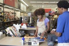站立在结算台扫描项目服务男性顾客的一个非裔美国人的女性售货员的画象 免版税库存照片
