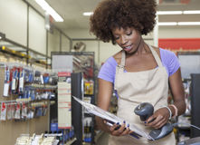 站立在结算台扫描项目的一个非裔美国人的女性售货员的画象 免版税库存图片