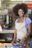 站立在结算台扫描项目的一个非裔美国人的女性售货员的画象 库存照片