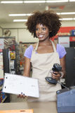 站立在结算台的一个非裔美国人的女性售货员的画象 免版税库存照片