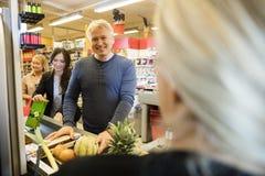 站立在结算台的男性顾客在超级市场 免版税库存图片