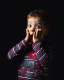 站立在黑背景的惊奇的男孩 免版税库存图片