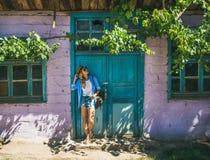站立在紫色墙壁附近的女孩在土耳其村庄在夏天 免版税库存照片