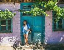 站立在紫色墙壁附近的帽子的女孩在土耳其村庄 免版税库存照片