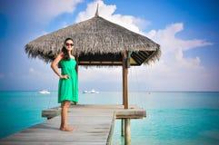 站立在绿色礼服的年轻亚裔看的妇女画象近的小屋在美丽的热带海滩 马尔代夫 免版税库存照片