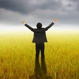 站立在黄色米领域和Rainclouds的愉快的商人 库存图片