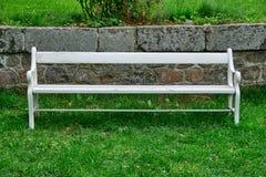 站立在绿色草坪的木头白色长凳 免版税图库摄影