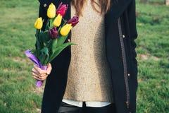 站立在绿草和举行b的外套的年轻亭亭玉立的妇女 库存照片
