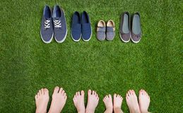 站立在绿草的家庭腿和鞋子 免版税库存照片