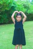 站立在绿草的逗人喜爱的小女孩和培养她的手做心脏塑造在头顶上有阳光背景 图库摄影
