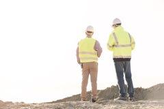站立在建造场所的建筑师背面图反对清楚的天空 免版税库存照片