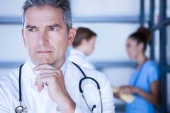 站立在医院的体贴的医生 免版税库存照片