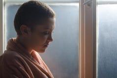 站立在医院窗口前面的年轻癌症患者 免版税库存照片