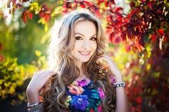 站立在autu的一个公园的美丽的典雅的年轻白肤金发的妇女 免版税库存图片