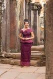 站立在Bayon寺庙的高棉礼服的柬埔寨女孩在吴哥市 库存图片