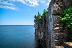 站立在Cyprus湖的大长的岩石峭壁看法反对蓝色明亮的天空在美丽的华美的布鲁斯半岛,安大略 免版税库存照片